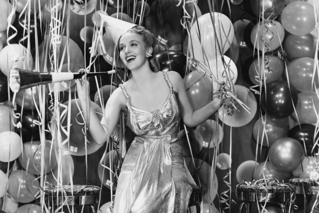 A retro party girl, in front of streamers and balloons