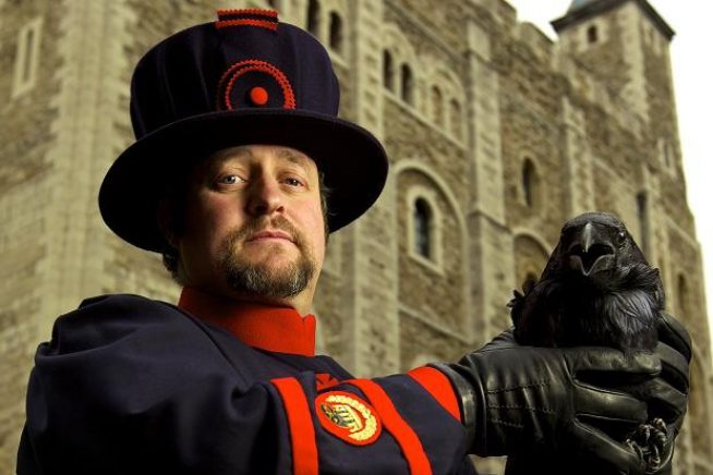 Image of author Christopher Skaife in from of the Tower of London with a raven
